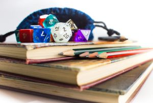 Close up of multicolored Dice with dice bag and Pencils on top of three Books