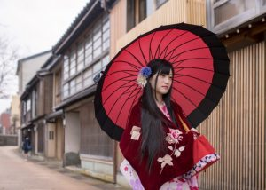 Young woman in kimono walking in traditional Japanese town.
